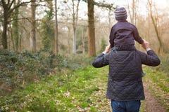 Großväterlicher tragender Enkel auf Schultern während des Wegs Lizenzfreie Stockfotos