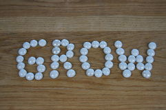 GROW. The word GROW written in white glass pebbles on a wooden background Stock Photos