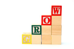 Grow. Word grow formed by alphabet wood blocks on a white surface Stock Photo