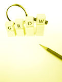Grow concept. A conceptual photograph of the word grow, spelt out in blocks of increasing height.  Taken with magnifying glass and pencil, on background with Stock Image