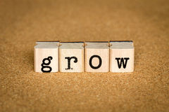 Grow Concept. Alphabet stamp on a cork board Stock Photography