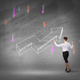 Grow and success concept. Rear view of businesswoman drawing increasing graph Royalty Free Stock Photo