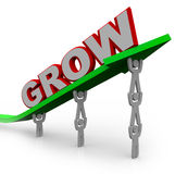 Grow - Teamwork People Reaching Goal. A team of people lift an arrow and the word Grow, symbolizing the growth that can be achieved with many team members Royalty Free Stock Photo