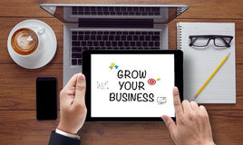 GROW YOUR BUSINESS CONCEPT. On the tablet pc screen held by businessman hands - online, top view Royalty Free Stock Images