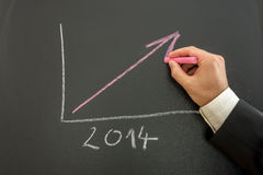 Growing business graph. Closeup of businessman drawing growing financial business graph for year 2014 Stock Photography