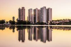 Growing city with few tall buildings reflected on the water of a. Lake, sunset hour - golden hour. Campo Grande MS, Brasil Stock Photo