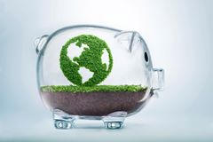 Growing clean eco planet Earth fund concept. Grass growing in the shape of planet Earth, inside a transparent piggy bank, symbolising the need to invest in the Royalty Free Stock Photos