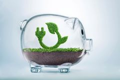 Growing clean energy fund concept. Grass growing in the shape of a plug and a leaf, inside a transparent piggy bank, symbolising the need to invest in the Royalty Free Stock Image