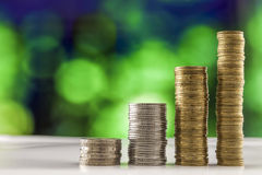 Growing coins stacks with green and blue sparkling bokeh backgro. Und. Financial growth, saving money, business finance wealth and success concept royalty free stock photography