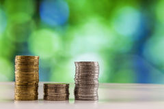 Growing coins stacks with green and blue sparkling bokeh backgro Stock Photography