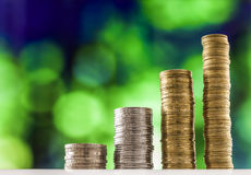 Growing coins stacks with green and blue sparkling bokeh backgro Royalty Free Stock Images