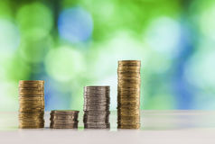 Growing coins stacks with green and blue sparkling bokeh backgro Stock Images