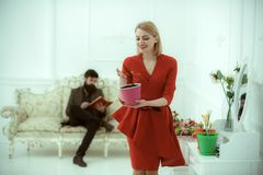 Growing concept. woman hold flower growing in pot while man reading book on sofa. Pot plant growing. Active growing. Growing concept. women hold flower growing stock photography