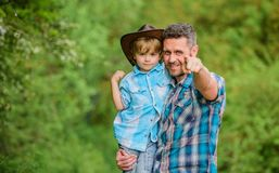 Growing cute cowboy. Small helper in garden. Little boy and father in nature background. Spirit of adventures. Strong. Like father. Power being father. Child royalty free stock photo
