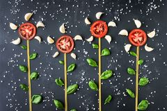 Growing flowers made from pasta, tomato and basil on a dark background. The concept of products. Growing flowers made from pasta, tomato and basil on a dark stock photo