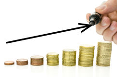 Growing interest rate. Growing stacks of Euro coins with black rising arrow over them. With copy space Stock Photo