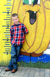 Growing by Leaps and Bounds. Little boy stands next to a growth chart.  He is smiling and is wearing a red plaid shirt Royalty Free Stock Images