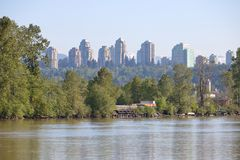 City Skyline and River Frontage. A growing modern city is the backdrop to a river lined with industry and trees Stock Images