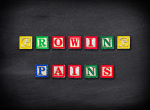 Growing pains. Concept on blackboard Royalty Free Stock Photos