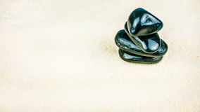 Growing piled up of four black pebbles on bright white sand. Light reflection on stone surface Stock Image
