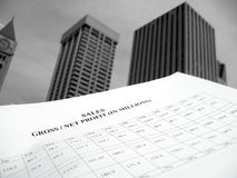 Growing Sales. Concept of a sales report against some corporate buildings. Black and white photo. Shallow depth of field.  Focus specifically on the title of the Royalty Free Stock Images