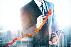 Growing sales. Businessman drawing upward red chart arrow on abstract city background. Growing sales concept. Double exposure Stock Images