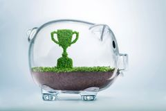 Growing succces investment concept. Grass growing in the shape of a trophy cup, inside a transparent piggy bank, symbolising the care, dedication and investment Royalty Free Stock Photography