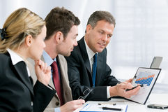 Growing successful business. Satisfied senior businessman showing growing chart at his happy colleagues in modern office Stock Photography