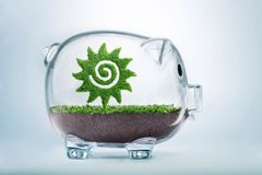Growing summer holiday fund concept. Savings for the summer holiday concept. Grass growing in the shape of the Sun, inside a transparent piggy bank, symbolising Royalty Free Stock Photos