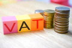 Growing taxes - colour blocks with VAT and money stacks. On table royalty free stock photography