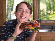 Growing Teenage Boy with Large Sandwich Stock Photography