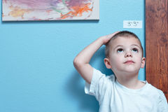 Growing Up. Little boy checking his height against a wall royalty free stock images