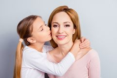 Growing-up beauty positivity respect gentle emotions health care. Concept. Close up portrait of pretty adorable nice mommy and small lovely girl kissing cheek Stock Photo
