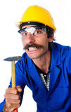 Growling Carpenter/Construction Worker With Hammer. A growling carpernter/construction worker wearing a yellow hard hat, safety goggles and a blue jumpsuit with Royalty Free Stock Photos