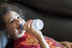 Grown child drinking milk in a bottle Royalty Free Stock Photos