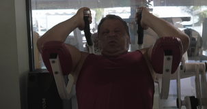 Grown man in the gym performing exercises on the upper abs. On exerciser for crunches stock video