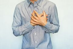 Men with symptoms of acute recurrent heart attack. Grown men with symptoms of acute recurrent heart attack. guy clinging heart on a blue background. chest pain Stock Photos