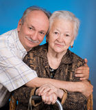 A grown son with his aging mom. On a blue background royalty free stock images