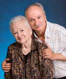 A grown son with his aging mom. On a blue background stock photography