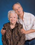A grown son with his aging mom. On a blue background royalty free stock photography