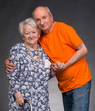 A grown son with his aging mom. On a gray background royalty free stock photos