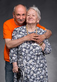 A grown son with his aging mom. On a gray background royalty free stock images
