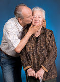 A grown son kissing his aging mom Stock Photos