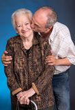 A grown son kissing his aging mom. On a blue background Stock Photos
