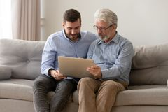 Grown son and senior dad using laptop at home together. Millennial son and elderly father sit on couch at home using laptop together, young men spend time with stock photography