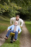 Grown up son pushing father in wheelbarrow Royalty Free Stock Photos