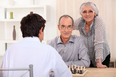 Grownup family playing chess. At home stock photo