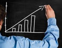 Growth. Man drawing a rising arrow on a blackboard Stock Image