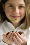 Growth. Beautiful teenager holding seedling in hands royalty free stock image