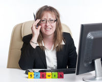 Growth in business. Business woman in office situation looking very pleased with herself and the word growth spelt out on her desk Stock Photo
